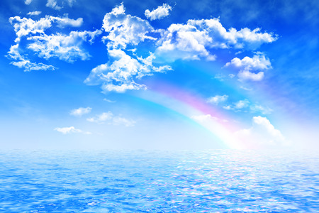 water reflection: two colorful rainbow on blue sky with cumulus clouds, reflection in water