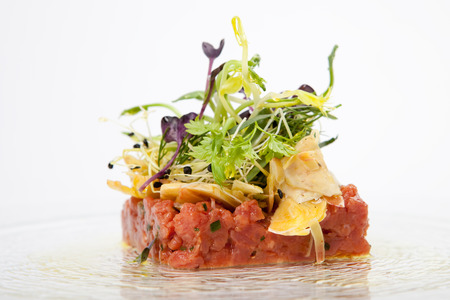 gastronomic: appetizer with tartar of veal tenderloin, decorated with artichokes and salad of fresh herb