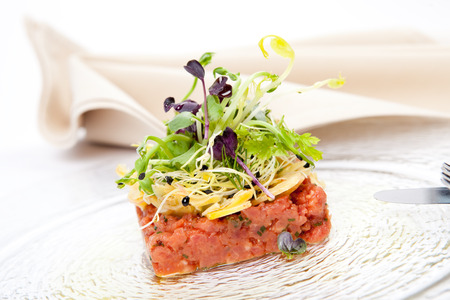 gastronomic: tartar made of veal tenderloin fillet, with fresh garden salad and artichokes Stock Photo