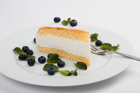 blue berry: cheese cake with blue berry and mint decoration on white plate, white background Stock Photo