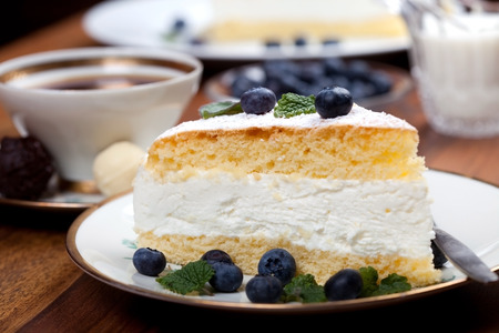 blue berry: cheese cake with blue berry and mint on a wooden table with a cup of coffee and milk