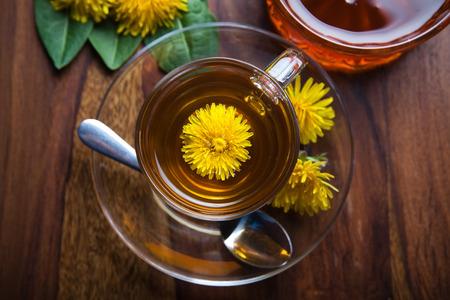木製テーブルの上のティーカップの中新鮮な黄色の花を持つタンポポ ハーブ茶紅茶