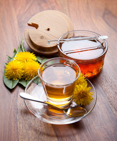 yellow blossom: herbal tea and honey made of dandelion, with yellow blossom and green leaf on wooden table Stock Photo