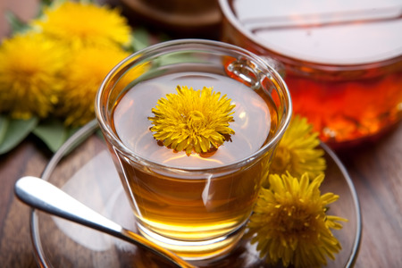 dandelion herbal tea with honey and blossoms on wooden table Stockfoto