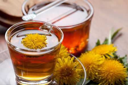 herbal tea infusion of fresh dandelion leaf, with yellow blossoms and honey