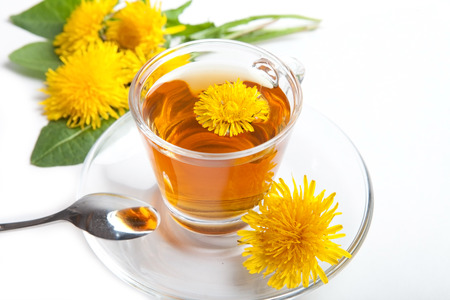 healthy dandelion tea with yellow blossom in teacup, white background, isolated
