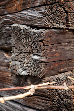node: corner node of overlapping wooden beams on veneer of ancient wooden house, close up