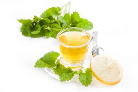 melissa tea in transparent tea cup with slice of lemon and green lemon balm on white background Stock Photo