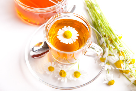herbal background: healthy herbal tea with blooming chamomile on white background, with blossom in teacup and honey,