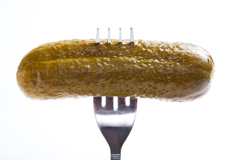pickled cucumber on a silver fork, white background, isolated, Banco de Imagens