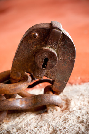 ensuring: close up of old grungy padlock on chain, rusty texture