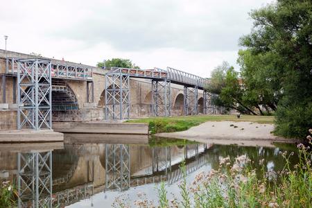 renewal: historic stone bridge in regensburg, germany with steel scaffolding for renewal Stock Photo