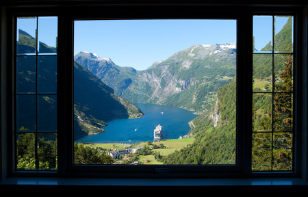 beach window: view through a window to geiranger fjord in norway with a cruise ship