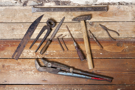 old and rusty work tools on wooden flooring