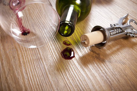 red wine stain: red wine stain on wooden flooring, with empty wine glass and bottle, retro corkscrew