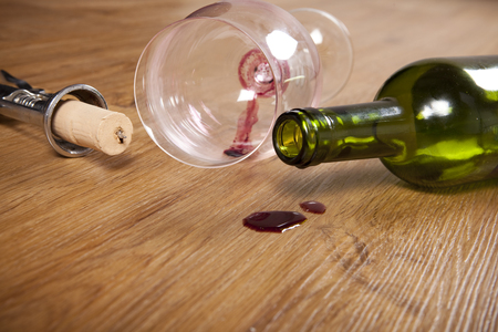 red wine stain: red wine stain on wooden flooring, with dirty wine glass, corkscrew and empty wine bottle,