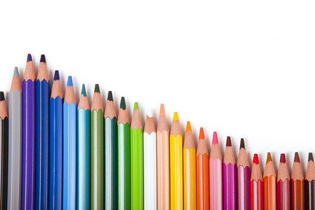 colored pencils in a row on white background, copy space