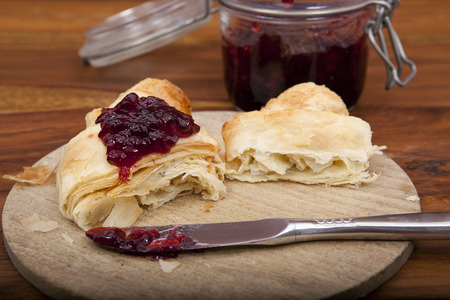 halved croissant and knife with cherry marmalade on wooden plate Stock Photo
