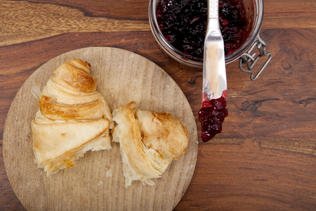 croissant with cherry marmalade on wooden background