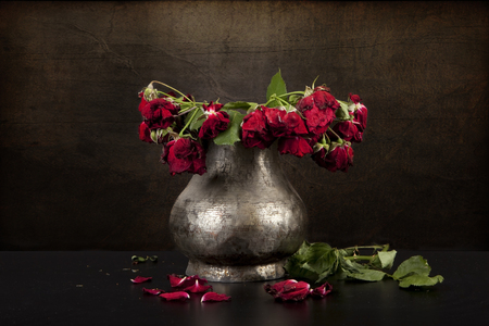 bouquet of dead red roses in pewter vase with grunge background