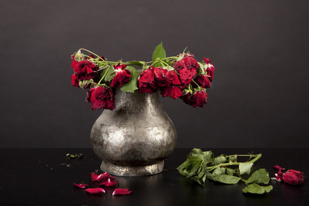 bouquet of dead red roses in pewter vase on black  background