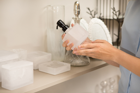 Cropped close up of a woman holding soap dispenser examining it while shopping at houseware store for bathroom accessories copyspace home consumerism purchase decor interior coziness buy