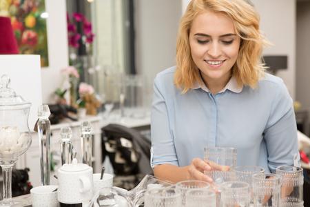Happy young beautiful woman smiling joyfully choosing glassware at the local store copyspace houseware dinnerware champagne housewife buyer customer consumer shopper shopaholic lifestyle