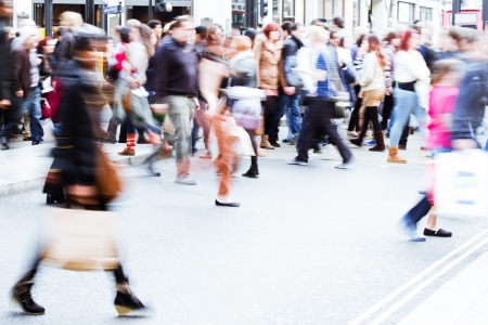 shopping crowd crossing the city street in motion blur photo