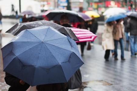 重い雨が傘を歩いて街の人々