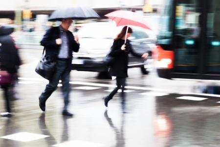 hurried people crossing the rainy street