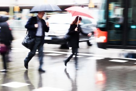 hurried people crossing the rainy street