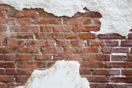 run down: background texture of cracked plaster at a brick wall