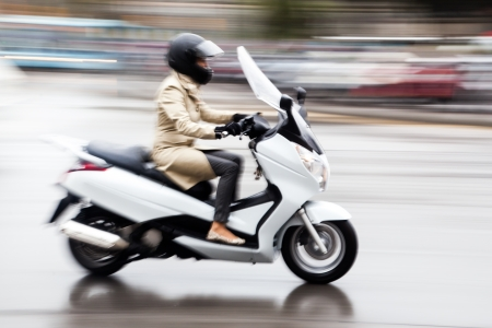 woman rides a scooter in motion blur