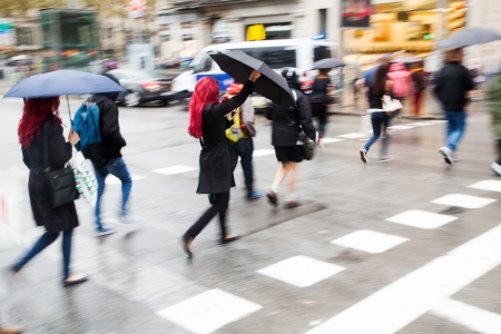 walking zone: people in motion blur crossing the rainy street with umbrellas Stock Photo