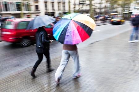 lluvia paraguas: dos mujeres con el paraguas en la lluvia
