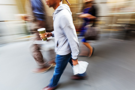 lunch hour: picture in motion blur of a man walking on the sidewalk with beverage and packed lunch at lunch hour