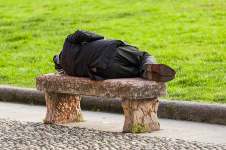 homeless person: homeless person sleeping on a stone bench