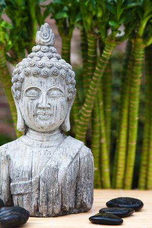 cabeza de buda: busto de Buda con masaje de piedras y bambú en el fondo