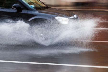 モーション ブラーの水しぶきで濡れている通りに車の運転