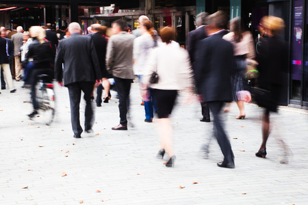 suited up: crowd of dressed up people in motion blur walking to a concert Stock Photo