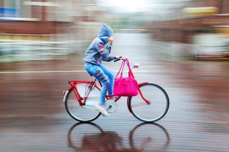 rain wet: bicycle rider at a rainy day in motion blur Stock Photo