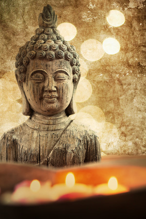 busts: attractive textured picture of a Buddha figure with floating candles in a stone bowl