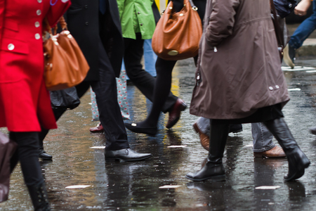 crossing arms: people crossing the street on a rainy day Stock Photo