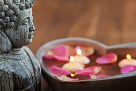 buddha head: buddha head with stone heart, filled with water, rose petals and floating candles Stock Photo