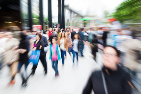 multitud: multitud de personas que hacen compras en la ciudad con efecto zoom