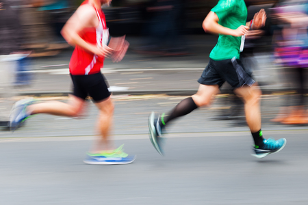 blur effect: picture with creative motion blur effect made by camera of running people at a city marathon