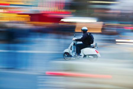 夕暮れ時にぼやけ都市交通でスクーター 写真素材