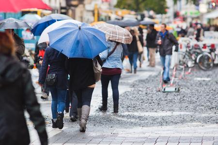 雨の多い街で傘を持つ人々 写真素材