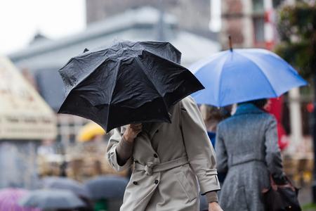 estado del tiempo: la gente que camina con los paraguas en la ciudad lluviosa