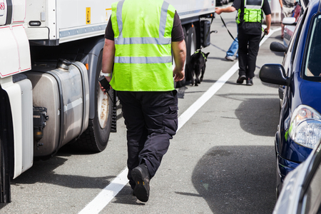 detection: security personnel walking with a detection dog along lorries at a ferry port gate